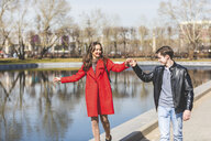Russia, Moscow, couple dating and having fun at park, young man holding woman's hand - WPEF00415