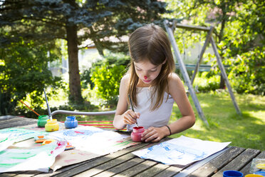 Little girl painting at table in the garden - LVF07087
