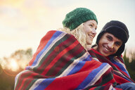 Portrait of romantic young camping couple wrapped in blanket - CUF28628