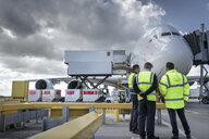 Ground crew inspecting A380 aircraft on stand in airport - CUF28732