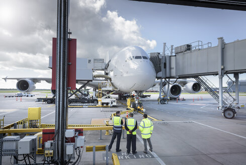 Ground crew inspecting A380 aircraft on stand in airport - CUF28738