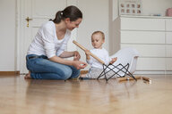 Mother and daughter assembling a chair at home - DIGF04583