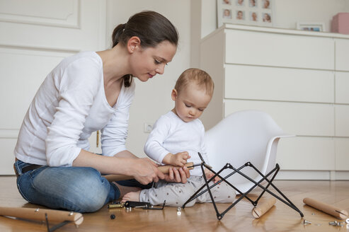 Mother and daughter assembling a chair at home - DIGF04586
