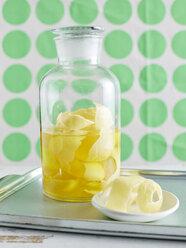 Lemon peel infusing in large glass jar to make limoncello - CUF29064