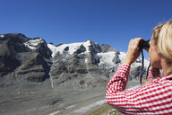 Austria, Carinthia, woman looking through binoculars pointing at Großglockner peak and Pasterze glacier, view from Kaiser-Franz-Josefs-Hoehe, High Tauern National Park - GWF05533
