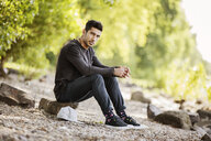 Portrait of young man sitting in nature - JATF01043