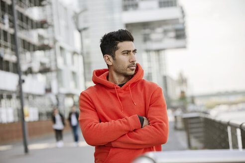 Portrait of fashionable young man wearing red hooded jacket - JATF01046