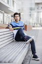 Portrait of fashionable young man sitting on bench - JATF01049