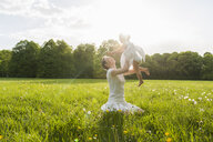 Mother and daughter playing on meadow in summer - DIGF04597