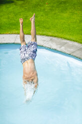 Back view of man jumping into swimming pool - MMAF00393