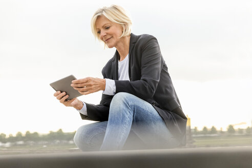 Smiling senior businesswoman sitting with tablet outdoors - FMKF05137