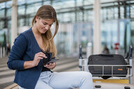 Smiling young businesswoman sitting outdoors with cell phone and suitcase - DIGF04607