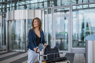 Smiling young woman pushing luggage trolley looking around - DIGF04610