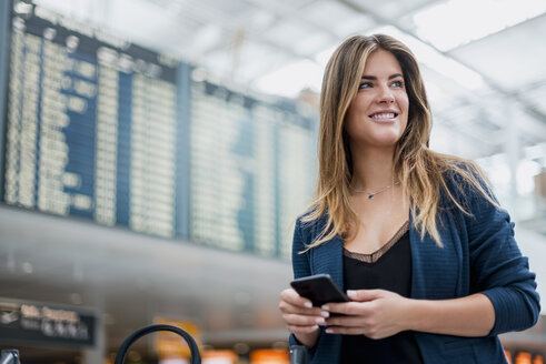 Smiling young woman with cell phone at departure board looking around - DIGF04613