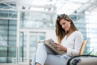 Young businesswoman sitting outdoors with suitcase reading newspaper - DIGF04619