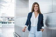 Portrait of smiling young businesswoman with luggage - DIGF04622