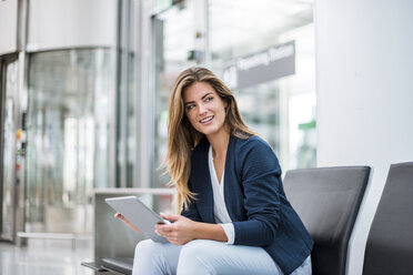 Young businesswoman sitting at waiting area using tablet - DIGF04625