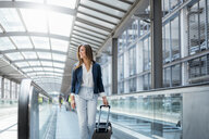 Smiling young businesswoman with baggage on moving walkway - DIGF04628