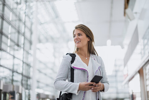Portrait of smiling young businesswoman with cell phone at the airport looking around - DIGF04634