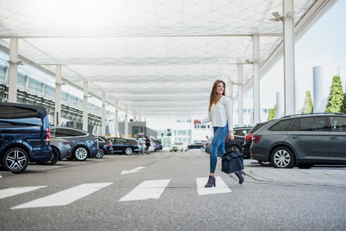 Young woman with bag crossing street at zebra crossing - DIGF04643