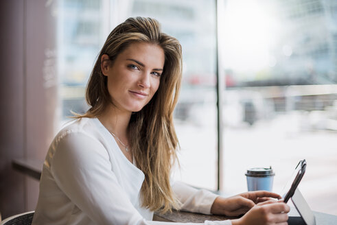 Portrait of smiling young businesswoman in a cafe using tablet - DIGF04646