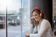 Happy young woman listening to music with headphones - DIGF04652