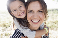 Portrait of mature woman giving daughter piggy back in park - CUF29088