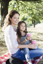 Portrait of mature woman and daughter drinking from paper cups at park picnic - CUF29091
