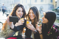 Three young women giggling for smartphone selfie at waterfront cafe - CUF29199