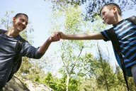 Male hiker giving son a helping hand in forest - CUF29274