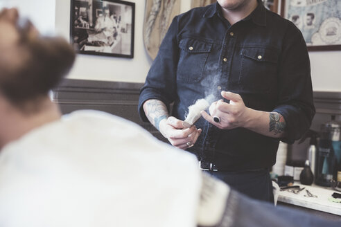 Barber preparing shaving brush in barber shop - CUF29301