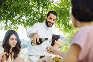 Group of friends having meal together, outdoors, man pouring champagne - CUF29316