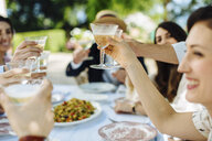 Group of friends having meal together, outdoors, hands raised, making toast - CUF29319