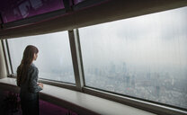 Businesswoman looking through skyscraper office window at Shanghai cityscape, China - CUF29391