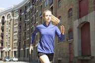 Runner jogging past building block, Wapping, London - CUF29406