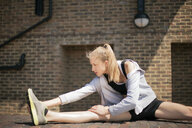 Runner stretching on walkway, Wapping, London - CUF29412