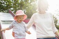 Mother and female toddler on park slide - CUF29445