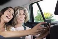 Senior woman and daughter taking smartphone selfie in car - CUF29454