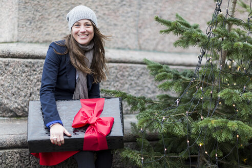 Portrait of mature woman with Christmas gift next to Christmas tree - CUF29469