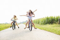 Girls cycling on country road - CUF29607