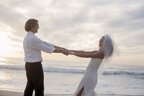 Bride and groom on beach, holding hands, fooling around, laughing - CUF29712