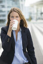 Portrait of young businesswoman drinking takeaway coffee - CUF29742