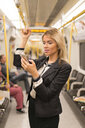 Businesswoman texting on tube, London Underground, UK - CUF29748