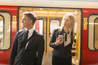 Businessman and businesswoman alighting train, London Underground, UK - CUF29751