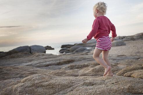 Female toddler toddling on coastal rock, Calvi, Corsica, France - CUF29835
