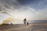 Mature man strolling with his toddler daughter on beach at sunset, Calvi, Corsica, France - CUF29838