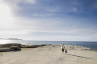 Mature man strolling with his toddler daughter on beach, Calvi, Corsica, France - CUF29841