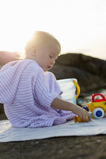 Female toddler sitting on beach playing with toy bucket - CUF29847