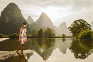 Young woman paddling in Li river, Yangshuo, Guangxi Zhuang, China - CUF29856