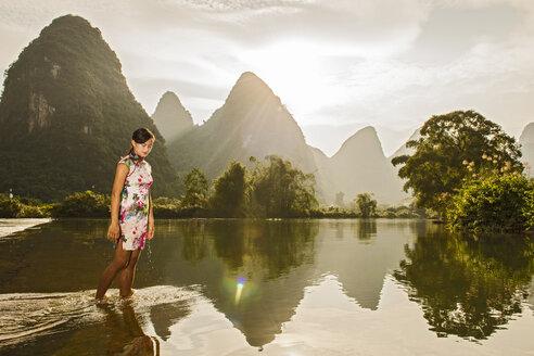 Young woman paddling in Li river, Yangshuo, Guangxi Zhuang, China - CUF29856